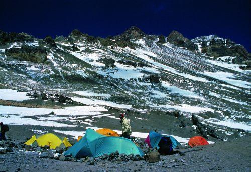 Widok z Nido de Condores na północne zbocza Aconcagui, którymi wiedzie droga normalna na szczyt; na I planie Piotr Pustelnik przy namiociku-trumience